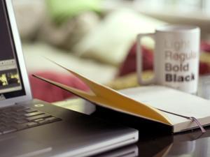 laptop beside notebook and coffee mug